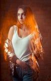 Donna castana attraente che posa allo studio scuro alla luce mista t Immagine Stock Libera da Diritti