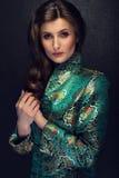 Donna castana attraente che posa nello stile giapponese alla moda J fotografia stock libera da diritti