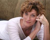 Donna castana attraente che si rilassa sullo strato con il libro Immagini Stock