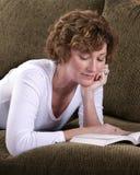 Donna castana attraente che si rilassa sullo strato con il libro Immagine Stock Libera da Diritti