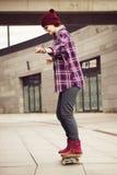 Donna castana in attrezzatura dei pantaloni a vita bassa che scateboarding sulla via Immagine tonificata Fotografia Stock Libera da Diritti