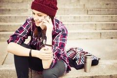 Donna castana in attrezzatura dei pantaloni a vita bassa che si siede sui punti e che parla sul telefono sulla via Immagine tonif Fotografie Stock