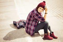 Donna castana in attrezzatura dei pantaloni a vita bassa che si siede sui punti e che parla sul telefono sulla via Immagine tonif Fotografia Stock