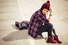 Donna castana in attrezzatura dei pantaloni a vita bassa che si siede sui punti e che parla sul telefono sulla via Immagine tonif Fotografia Stock Libera da Diritti