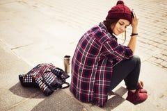 Donna castana in attrezzatura dei pantaloni a vita bassa che si siede sui punti sulla via Immagine tonificata Fotografia Stock