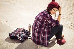 Donna castana in attrezzatura dei pantaloni a vita bassa che si siede sui punti sulla via Immagine tonificata Immagini Stock Libere da Diritti
