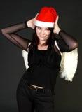 Donna castana in cappello di Santa con le ali bianche Immagini Stock