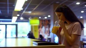 Donna castana che beve succo d'arancia fresco da vetro di plastica, dieta antiossidante immagini stock libere da diritti