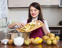 Donna castana che cucina l'inceppamento della pera Fotografia Stock