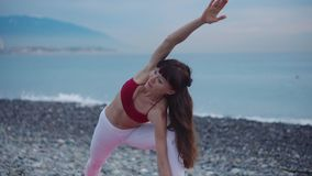 Donna castana che fa yoga all'aperto sulla spiaggia stock footage
