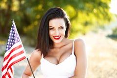 Donna castana che giudica la bandiera di U.S.A. all'aperto Fotografia Stock Libera da Diritti