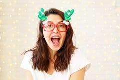 Donna castana che indossa i vetri divertenti di carnevale per la celebrazione di Natale immagini stock libere da diritti