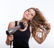 Donna castana che mette in piega capelli lunghi Fotografia Stock