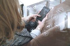 donna castana che per mezzo dello Smart Phone e del computer digitale della compressa sopra Fotografia Stock