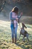 Donna castana che posa con il suo cane tedesco adorabile del puntatore Immagini Stock