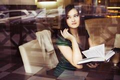 Donna castana che si siede al caffè studing e di bevanda del libro di lettura del caffè, Immagini Stock