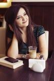 Donna castana che si siede al caffè studing e di bevanda del libro di lettura del caffè, Fotografie Stock