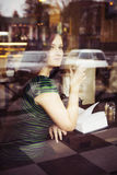 Donna castana che si siede al caffè studing e di bevanda del libro di lettura del caffè, Fotografia Stock