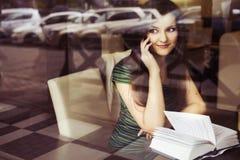 Donna castana che si siede al caffè studing e di bevanda del libro di lettura del caffè, e parlando sul telefono Immagini Stock