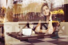 Donna castana che si siede al caffè studing e di bevanda del libro di lettura del caffè, e parlando sul telefono Fotografia Stock