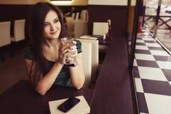 Donna castana che si siede al caffè studing e di bevanda del libro di lettura del caffè, ed aspettando qualcuno che sia in ritard Fotografie Stock Libere da Diritti