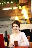 Donna castana che si siede alla tavola con il computer portatile Immagine Stock Libera da Diritti