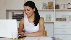 Donna castana che si siede alla tavola ed al lavoro video d archivio