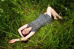 Donna castana che si trova sull'erba verde fotografia stock