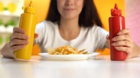 Donna castana che tiene ketchup e senape sul piatto delle patate fritte, pasto non sano fotografia stock libera da diritti
