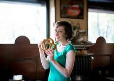 Donna castana che tiene una ciambellina salata Fotografie Stock Libere da Diritti