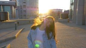 Donna castana con i balli lunghi dei capelli contro il contesto di un tramonto stock footage