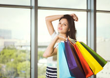 Donna castana con i sacchetti della spesa colourful dai negozi operati Vista panoramica nella sfuocatura sui precedenti Fotografia Stock Libera da Diritti