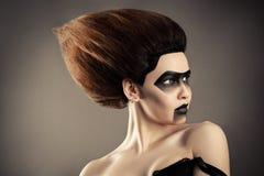 Donna castana con l'acconciatura di modo ed il trucco scuro creativo fotografia stock