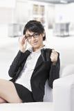 Donna castana con la tazza sul sofà all'ufficio Immagine Stock