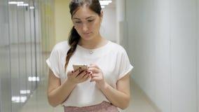 Donna castana con un telefono nel corridoio di un edificio per uffici stock footage