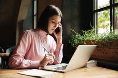 Donna castana concentrata che si siede dalla tavola con il computer portatile Fotografie Stock