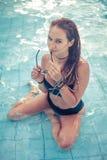 Donna castana in costume da bagno nero che si siede in acqua blu della piscina Immagine Stock