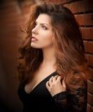 Donna castana dei giovani capelli marrone chiaro affascinanti in blusa nera vicino ad un muro di mattoni rosso Giovane donna sple Immagine Stock
