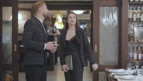 Donna castana di fascino in vestito e un uomo biondo barbuto bello nel redteurant moderno Progettista femminile che mostra a stock footage