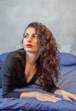 Donna castana elegante che si trova a letto Fotografie Stock