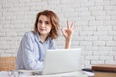 Donna castana felice che lavora al computer e che mostra segno giusto Immagine Stock