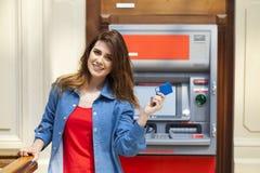 Donna castana felice che ritira soldi dalla carta di credito al BANCOMAT Immagine Stock