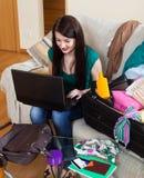 Donna castana felice che sceglie località di soggiorno online Immagine Stock Libera da Diritti