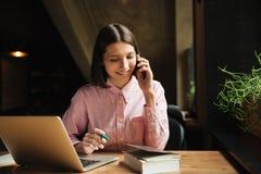 Donna castana felice che si siede dalla tavola con il computer portatile Immagine Stock Libera da Diritti