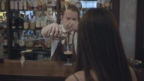 Donna castana irriconoscibile che si siede al contatore della barra Barista grassottello che versa due porzioni di caffè espresso stock footage