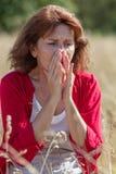 donna castana 50s che ha allergie del polline nel campo Fotografia Stock Libera da Diritti