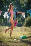 Donna castana sexy in bikini e camicia che mettono i vestiti per asciugarsi in sole Giovane femmina sensuale con le gambe lunghe  Immagini Stock