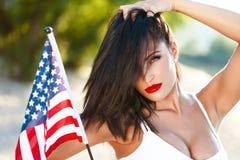 Donna castana sexy che giudica la bandiera di U.S.A. all'aperto Fotografia Stock Libera da Diritti