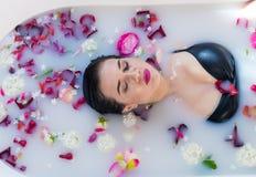 Donna castana sexy che si rilassa nel bagno caldo del latte con i fiori Fotografia Stock