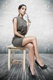 Donna castana sexy che si siede sulle feci Fotografia Stock